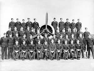 Four rows of men in dark military uniforms surrounding an aircraft's three-bladed propeller