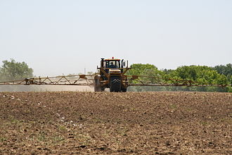 Pesticide application - Large self-propelled agricultural 'floater' sprayer, engaged in pre-emergent pesticide application