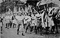 A group of youths marching with spiked bamboo, Indonesia.jpg
