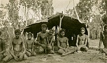 Groote Eylandt-History-Aboriginal boys and men in front of a bush shelter - NTL PH0731-0022