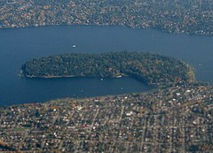 A forested peninsula surrounded by a lake and urban neighborhoods