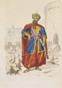 Ali Khoja, ruler of Algiers 1817-1818, resplendent in a green turban and wearing a fine sword, is surrounded by the severed heads of vanquished enemies after the bombardment of 1816 (C19).jpg