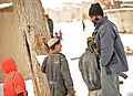 An Afghan National Police (ANP) officer talks to children carrying bags of rice and beans in Pinzo village, Nawbahar district, Zabul province, Afghanistan, Feb 120205-N-UD522-175.jpg