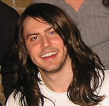 A close-up of a Caucasian adult male with long brown hair smiling.