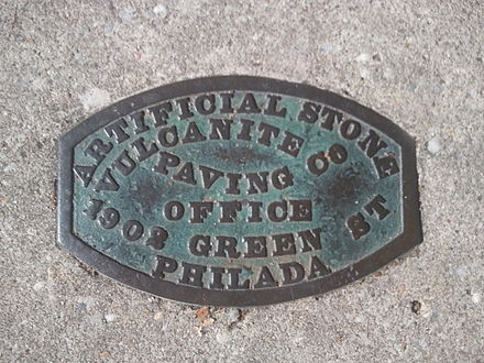 "A plaque set in the concrete of a sidewalk on Columbia Avenue in Cape May, New Jersey, USA. It reads ""Artificial Stone Vulcanite Paving Co, Office 1902 Green St, Philada"" [Philadelphia, Pennsylvania, USA]. It probably dates to the late 19th or early 20th centuries. (The concrete that currently surrounds it is not the original sidewalk.)"