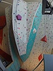 Vue plongeante panoramique d'un haut mur d'escalade en intérieur