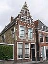 Pand met hoge verdieping onder zadeldak tegen trapgevel versierd met kant-, neg- en boogblokken