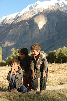 Three smiling young boys, with trees and a mountain in the background