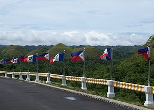 Flag of Bohol - Flags of Bohol and the Philippines near the Chocolate Hills. Note that the color of the star used in the flags is plain yellow, instead of the yellow-fimbriated blue star as dictated by law. The shade of blue used in this version is the same as that of the current shade of blue (royal blue) in the Philippine flag, which was only made official in 1998. However, when the specifications for the Bohol flag were described in 1969 the shade of blue of the Philippine flag was navy blue; most official versions of the Bohol flag use navy blue.
