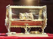 A mumified hand, with a strip decorated with pearls on it, in a gilded box