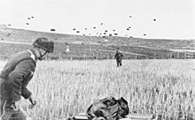 German paratrooper landing with others in the sky behind him