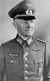 A man wearing a peaked cap, military uniform with an Iron Cross displayed at the front of his uniform collar.