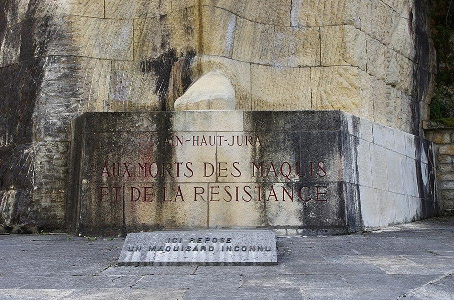 """Le Val d'Enfer.   46° 04′ 17″ Nord   5° 29′ 04″ Est    Le 19 août 1945, l'Association des Anciens du Maquis de l'Ain décide de construire un monument à la mémoire des 700 morts des Maquis de l'Ain et du haut Jura.   La première pierre du monument est posée le 26 juin 1949 par le général Koenig.   29 juillet 1951: inauguration du monument sous la présidence d'honneur de Madame veuve Chambonnet """"Didier"""" et la présidence de Monsieur Jean Saint-Cyr, ministre de l'agriculture, député de l'Ain, président du conseil général de l'Ain.  Le Président du Conseil Gaston Monnerville y présidera l'inhumation d'un maquisard inconnu le 29 mai 1954.   L'inauguration du cimetière des maquisards sera présidée par le général De Gaulle le 24 juin 1956.   L'oeuvre du Val d'Enfer, du sculpteur Charles Machet, a été financée, en plus des institutions,  par une participation ouvrière syndicale et des passants anonymes.  A l'est du monument s'étend le cimetière où reposent quatre-vingt-neuf maquisards morts au combat, dont trente-six inconnus  Sept Espagnols, deux Polonais, deux Italiens, un Russe, cinq Nord-Africains, venus combattre dans le maquis reposent au pied du mât où flotte le drapeau tricolore.   Cerdon (Ain).  Val d'Enfer.  46 ° 04 '17 """"Nord5 ° 29' 04"""" East  On 19 August 1945, the Alumni Association of the Maquis de l'Ain decided to build a monument to the memory of his dead 700 Maquis de l'Ain and Jura.  The first stone of the monument was placed June 26, 1949 by General Koenig.  July 29, 1951: Inauguration of the monument under the honorary presidency of the widow Chambonnet """"Didier"""" and chaired by Jean Saint-Cyr, Minister of Agriculture, deputy of the Ain, president of the council of Ain .  Council President Gaston Monnerville will chair the burial of an unknown maquisard May 29, 1954.  The inauguration of the cemetery maquisards will be chaired by General De Gaulle June 24, 1956.  The work of the Val d'Enfer, the sculptor Charles Machet was funded, in addition to institutions,"""