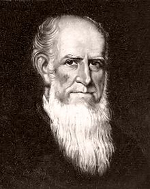 A balding man with a long, white beard