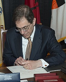 An image that shows Christopher Eisgruber signing a paper