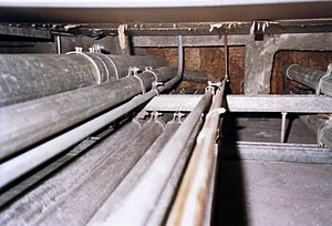 Electrical conduit - This illustration shows electrical conduit risers, looking up inside a fire-resistance rated shaft, as seen entering bottom of a firestop. The firestop is made of firestop mortar on top and mineral wool on the bottom. Raceways are used to protect electrical cables from damage.