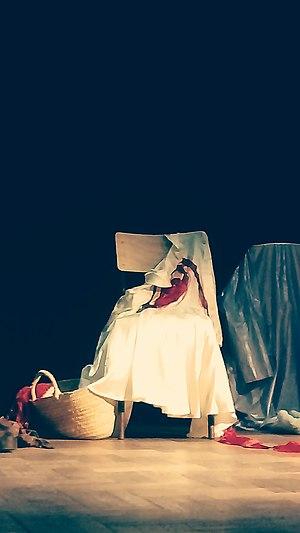 Sur une scène de théâtre, une chaise où est abandonnée une robe blanche ornée d'un ruban rouge. À ses pieds, un panier dont on voit sortir la chevelure rousse d'une poupée de chiffon.