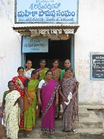 The directors of the Mulukanoor Women's Thrift Cooperative stand at the entrance to their credit union in Karimnagar district, Andhra Pradesh, India Credit Union in Warangal, India.JPG
