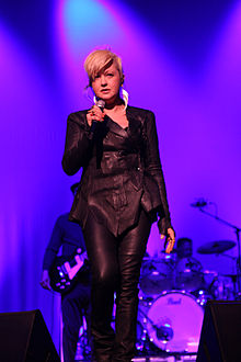 A blond woman with short hair singing in a black attire on stage. The background is bathed in violet lighting.