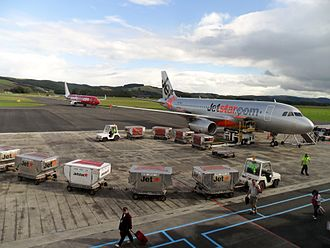 Dunedin Airport - A Jetstar Airbus A320 on the tarmac with a Virgin Australia Boeing 737 in the background