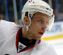 Head view of a hockey player in a white uniform and helmet as he stares intently into the distance.