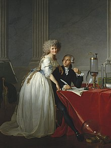 Full-length portraits of a man and a woman. The man is seated at a table covered with a bright red cloth, looking up at the woman, and she is looking out at the viewer. They occupy the bottom half of the painting, while the top half resembles marble and pillars. She is wearing a white dress with a blue sash and he is wearing a dark coloured suit. Glass chemistry equipment sits on the table and on the floor.