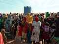 Displaced persons with water tank in Genenia, West Darfur in 2007.jpg