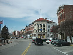 A row of two-story commercial brick buildings, some painted, on a street curving away from the viewer to the right and left. In front of them is a road, some short bare trees, and diagonally parked cars.