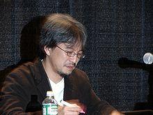 Een foto van een bebrilde Eiji Aonuma bij een microfoon