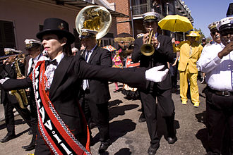 Second line (parades) - Local Jazz singer Jane Harvey Brown leads the way as grand marshal for a brass band at a second line in the French Quarter in New Orleans.