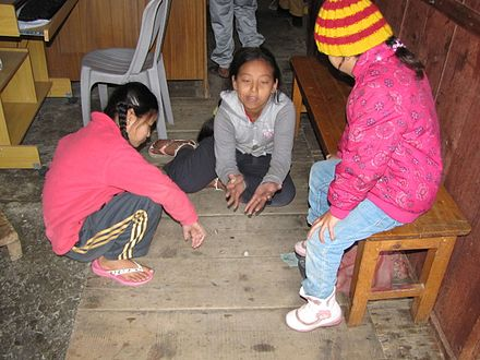 Nepali children playing a variant of knucklebones with pebbles. Five-stone in Nepal.jpg