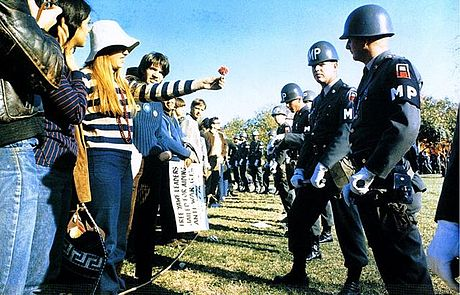 An anti-war demonstrator offers a flower to a Military Police officer during the National Mobilization Committee to End the War in Vietnam's 1967 March on the Pentagon Flower Power demonstrator.jpg