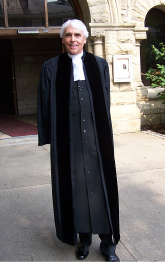 Geneva gown - A Presbyterian pastor wearing a Geneva gown over a cassock with white preaching tabs.