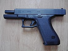 "A ""first-generation"" Glock 17 with the slide locked back displaying its vertical barrel tilt"