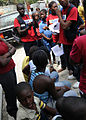 Haitian students in red shirts are teaching classes on sanitation and HIV prevention to residents of Port-au-Prince, Haiti, March 18, 2010 100318-N-HX866-005.jpg