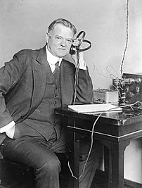 Herbert Clark Hoover listening to a radio {{de...