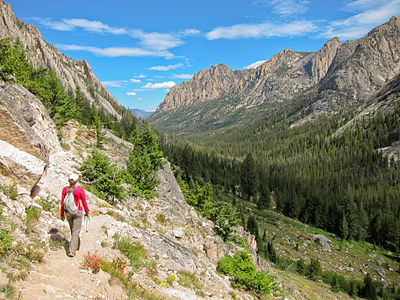 Hiker and Redfish Canyon from Alpine Lake trail in Sawtooth Wilderness