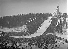 A view of a ski jump hill with crowds surrounding the landing area