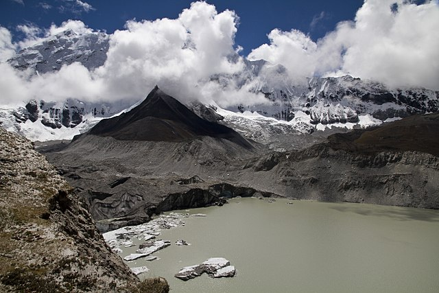 A view of the eastern extent of Imja Tsho. The image shows the Imja Glacier calving into the lake, as well as the surrounding peaks bathed in clouds.