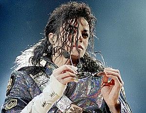 تصویری از مایکل جکسون که عینک را در دستش نگه داشتهاست.