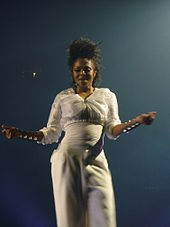 A woman, who wears a white blouse, belt and trousers, has her arms open (she has four bracelets on each arm).