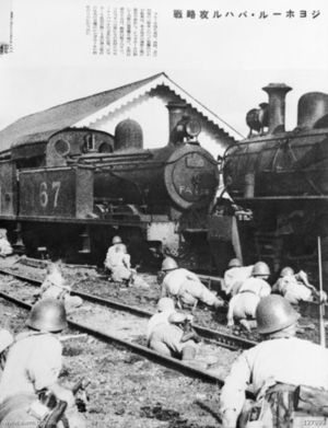 Japanese occupation of Malaya - Japanese troops take cover behind steam engines at the Johor railway station in January 1942