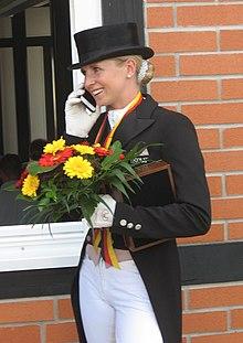 freundliche Dame mit schwarzem Hut, weißen Hosen, Frack und Blumen in der Hand bei einer Reit-Meisterschaft telefoniert