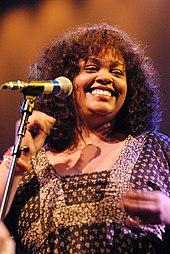 Eine Frau, die ein braunes Kleid trägt, während sie lächelt und ihre Finger schnippt.