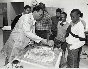 James E. Mayo - Mayo explains the silk-screen process to a group of prevocational trainees from the D.C. Association for Retarded Citizens, at the Anacostia Community Museum, 1985.