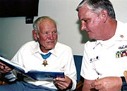 an older man wearing a medal of honor looks at a book while talking to another man wearing master chief summer whites