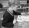 Jongen bezig met een postzegelverzameling, Bestanddeelnr 252-8770.jpg