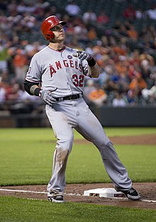 A man in a grey baseball jersey with the number 32 on the front right and a red batting helmet with the Angels logo.