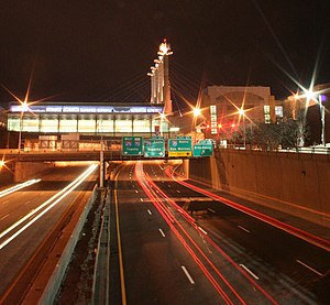 Interstate 670 (Kansas–Missouri) - Looking westbound on I-670 passing below the Bartle Hall Convention Center at night.