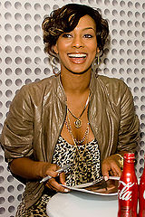 Keri Hilson wearing a leopard skin singlet and a brown jacket, signing a photo.